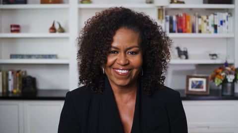 michelle obama with her curly hair wearing black jacket