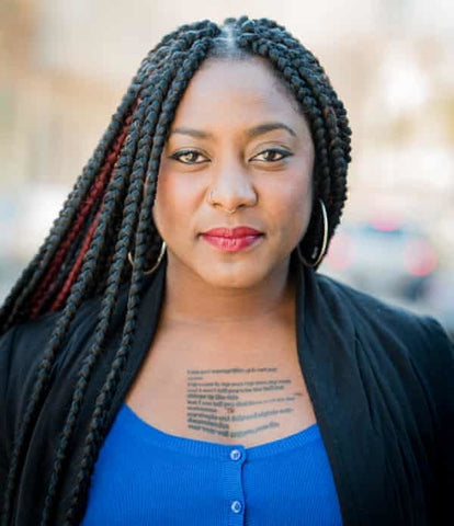 black woman alicia garza with chest tattoo wearing blue shirt and black jacket