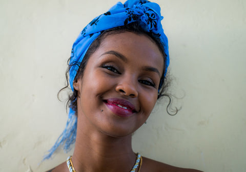 black women ilwad elman wearing a blue colored scarf wrapped her hair