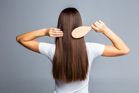 woman brushing her long and brown hair
