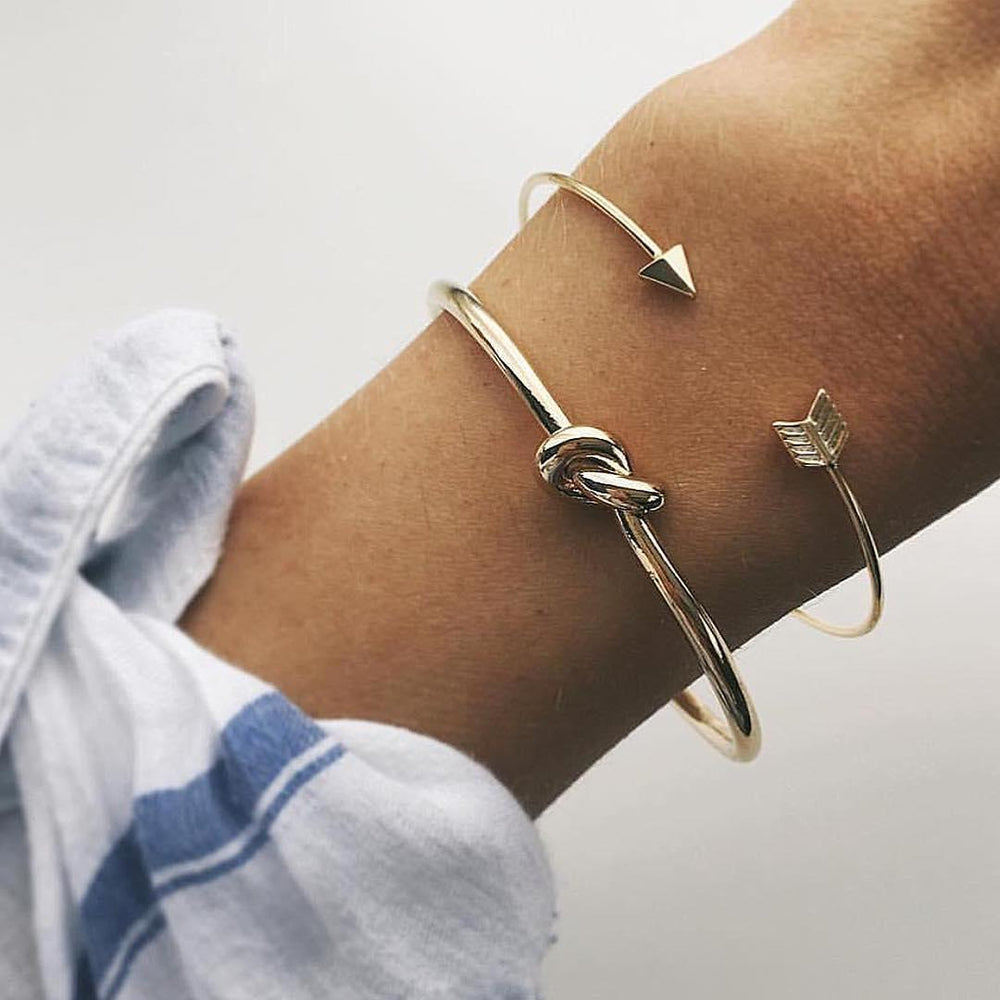 women is wearing an open-arrowed and knotted vintage gold colored two in one pack bracelets