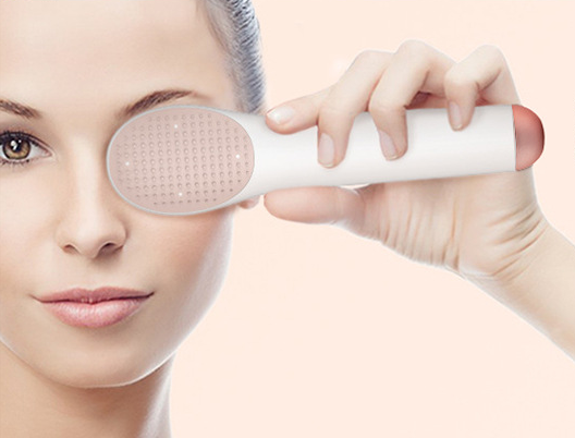Women holding white-colored eye and face massager with hot and cold therapy sonic vibration stick for facial massaging