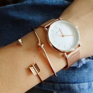women is wearing a gold watch and open-arrowed and knotted vintage gold colored two in one pack bracelets