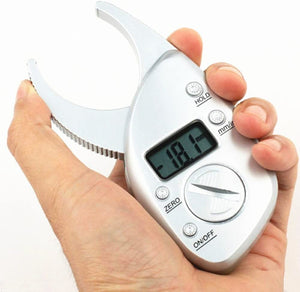 A man holding portable digital body fat caliper measurement tool shows the percentage on a monitor in his hand