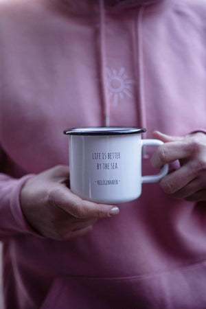 Emaille Tasse mit Spruch - Life is better by the sea - in Hand gehalten