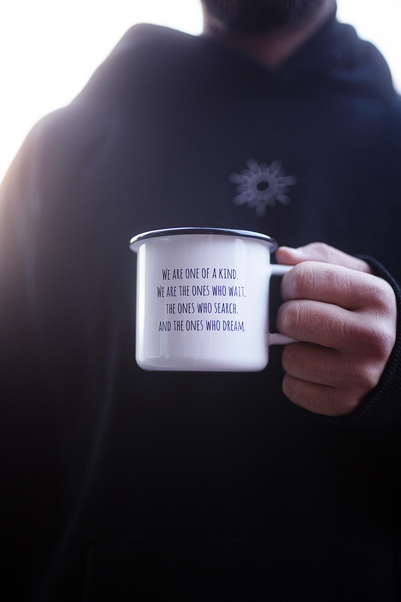 Emaille Tasse mit Spruch - We are one of a kind, we are the ones who wait, the ones who search and the ones who dream - in Hand gehalten.