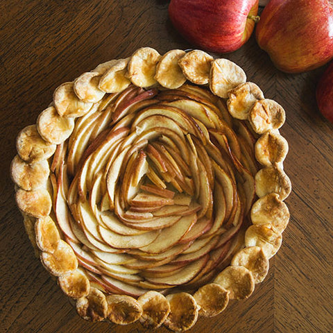 baked apple pie with spiral pattern made from apples, fresh whole apples on the side