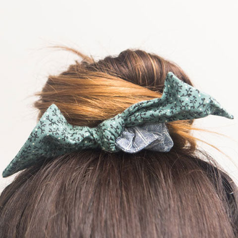 A hair bun is held with a fabric bow hair scrunchie in a green and blue fabric