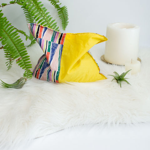 colorful cherry pit grain bag is surrounded by candles, air plants, and a fern on a faux fur blanket.
