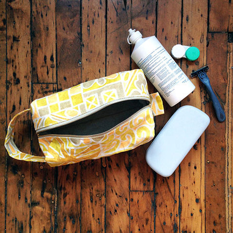 yellow patterned toiletry bag with contact solution bottle, contact case, and glasses case next to them on a wood floor