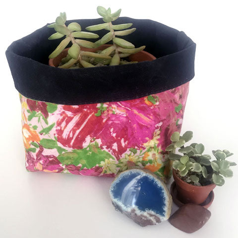 Pink and black waxed canvas organizer holds a succulent plant. A miniature succulent plant and blue geode sits next to the holder.