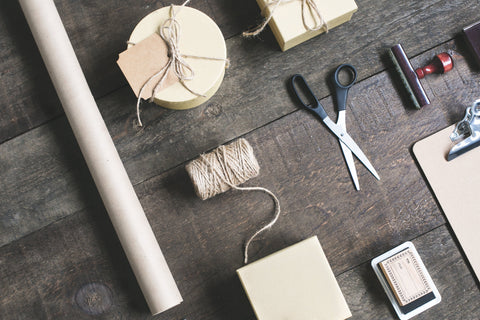 Twine, scissors, and paper all laid out and ready to wrap, pack, box, ship, move and deliver.