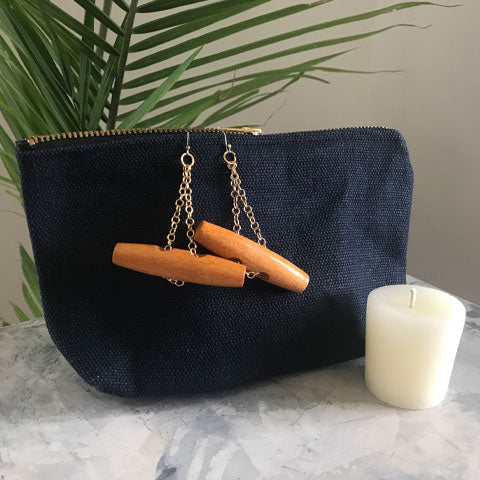 a pair of wood toggle and gold dangly earrings hang on an open zippered pouch in navy blue. A small votive beeswax candle sits in front. The items sit on a marble ground with a palm plant in the background.