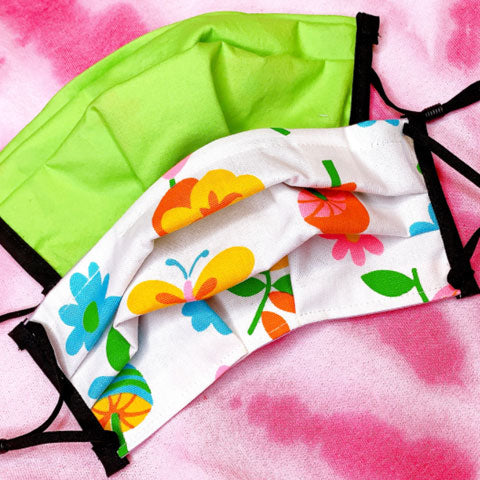 Pleated fabric face mask with adjustable ear loops feature vintage floral, fauna, and fruit print in bright colors on white. Inside of mask with lime green.