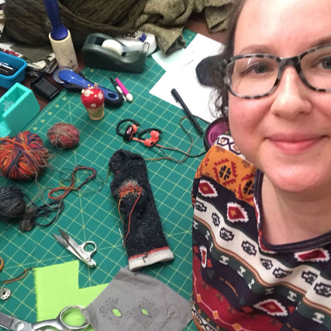 Woman smiles while looking up at camera. Behind her: a sock she is mending along with visible mending tools and supplies.