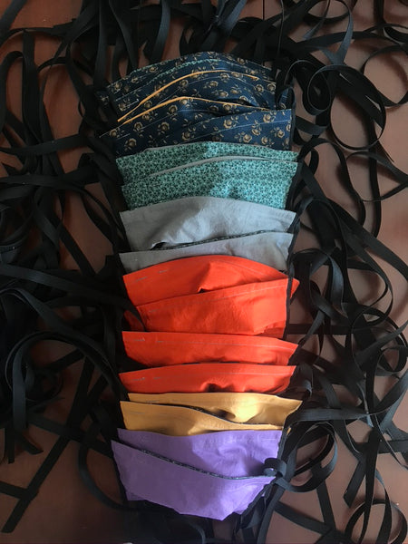 a column of cotton fabric face masks with black ties