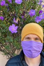 Load image into Gallery viewer, man wears a knitted yellow cap, purple face covering, and black puffy coat. He stands in front of a green bush with purple flowers.