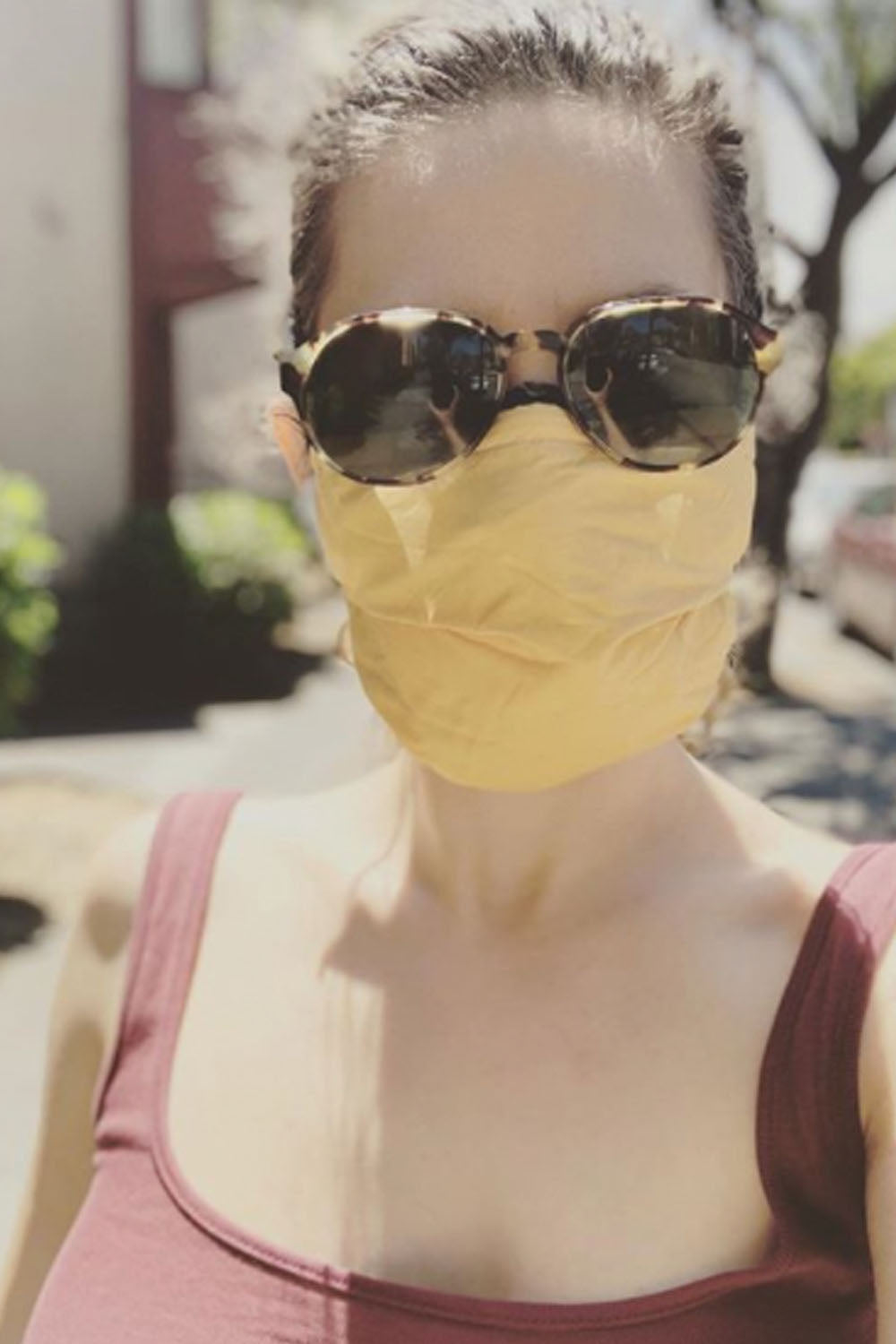 Woman in sunglasses and tank top wears light orange fabric face mask.