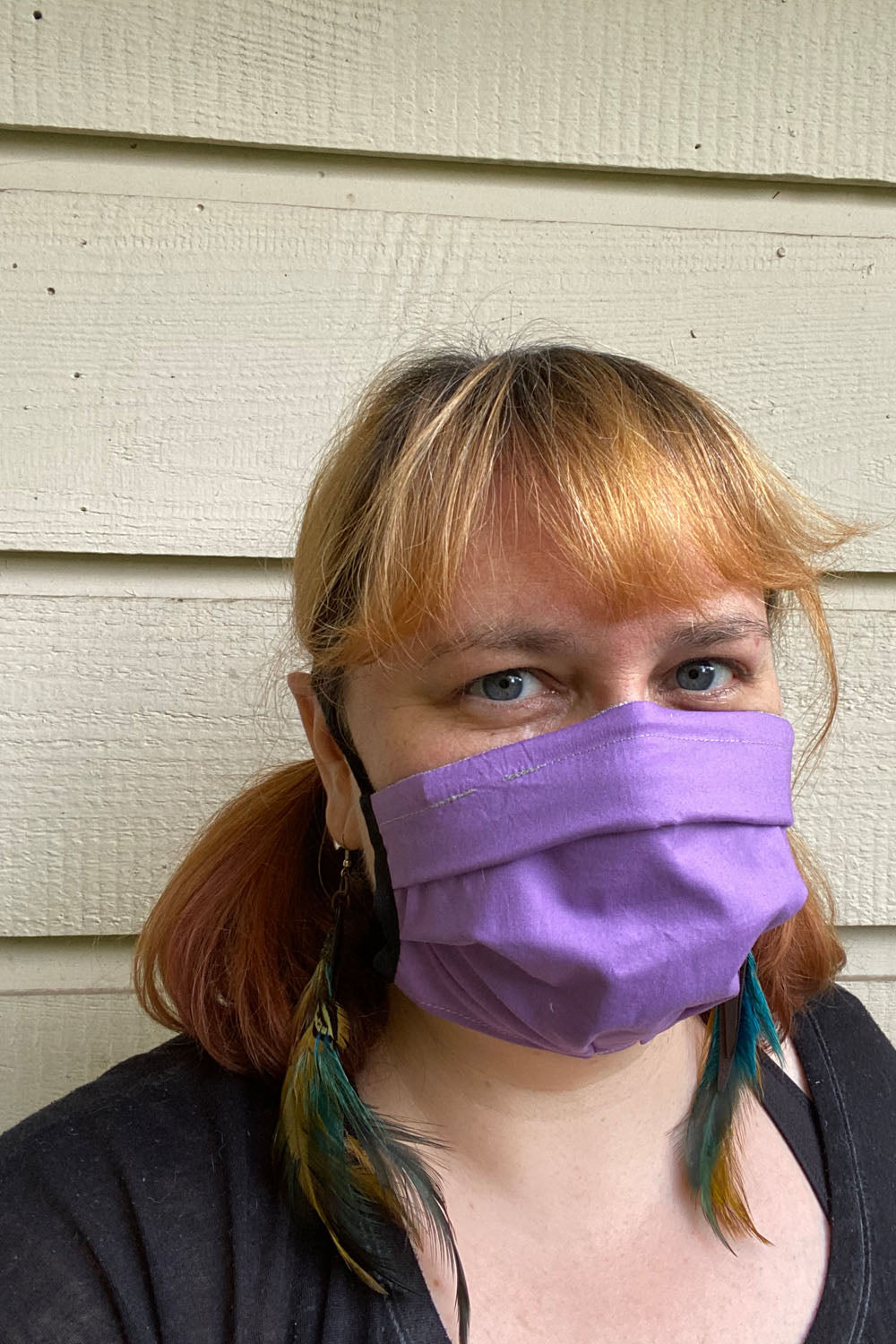 Woman wears a purple fabric face covering, feather earrings, and black t-shirt. She is smizing behind her mask. This is a portrait view of her. The background is a beige painted wood siding.