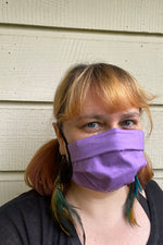 Load image into Gallery viewer, Woman wears a purple fabric face covering, feather earrings, and black t-shirt. She is smizing behind her mask. This is a portrait view of her. The background is a beige painted wood siding.