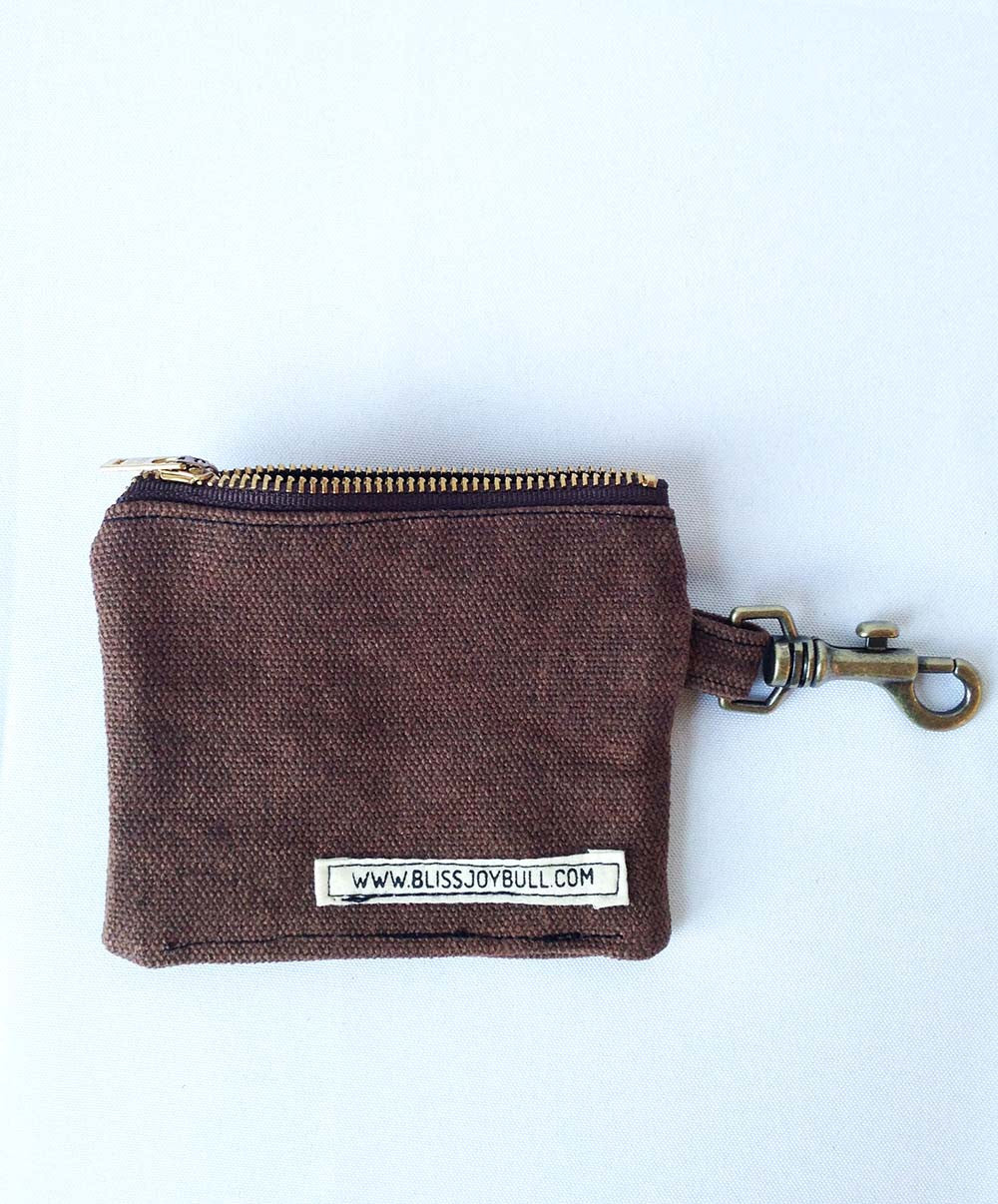 Back of wallet shows an open zipper at top, lobster claw clip at right side. Cotton label on bottom right of wallet reads www.blissjoybull.com