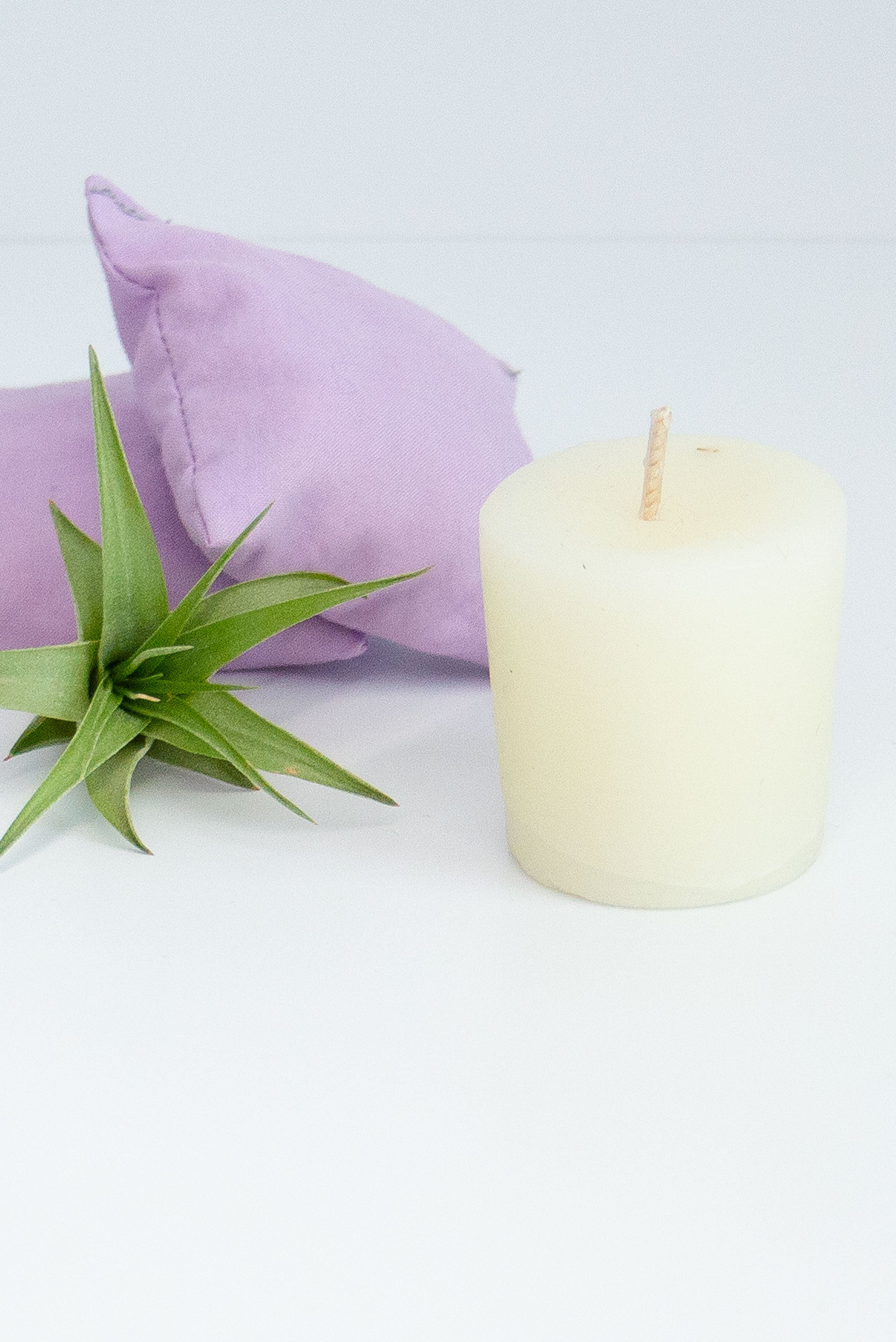A white votive candle sits next to an air plant and light purple reusable hand warmers on a white background.