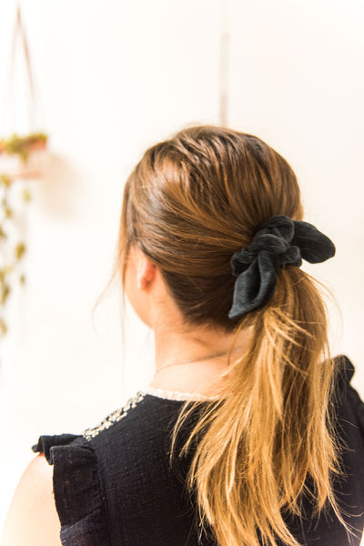 Woman faces away from camera. Her hair is tied in a mid-ponytail with a black velvet bow hair scrunchie.