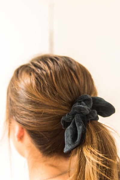 Close up of a woman facing away from camera. Her hair is tied in a mid-ponytail with a black velvet bow hair scrunchie.