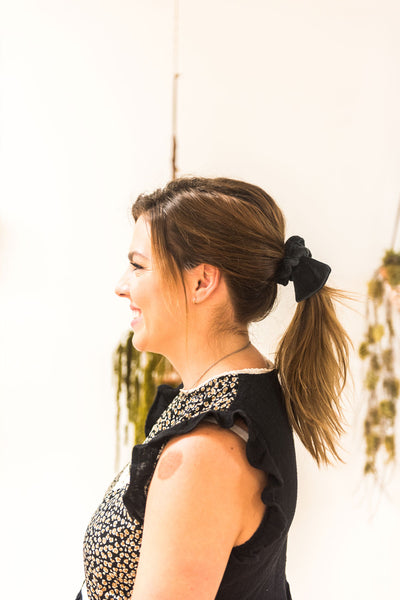 Side view of a woman with her hair tied in a mid-ponytail with a black velvet bow hair scrunchie. She is smiling.