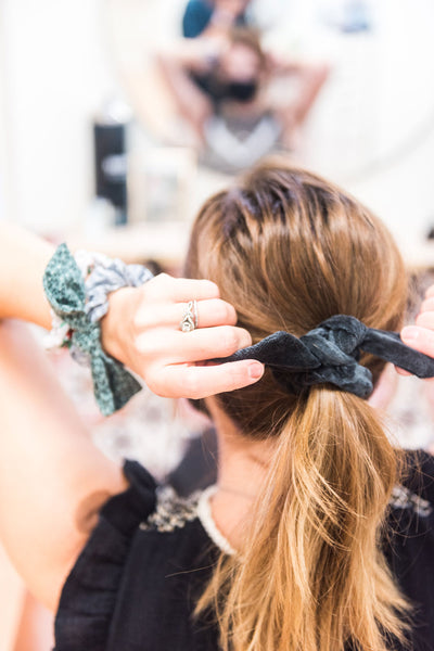 Back view of a woman tightening her ponytail. She wears a black velvet bow hair scrunchie in her hair. Two more hair scrunchies are on her left wrist.