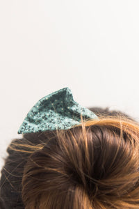 Close up of a woman wearing a bun in her hair. She wears a green printed fabric bow.