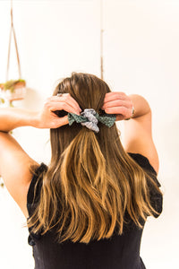 Back view of a woman adjusting her hair ponytail. She wears a blue and green fabric bow hair scrunchie.