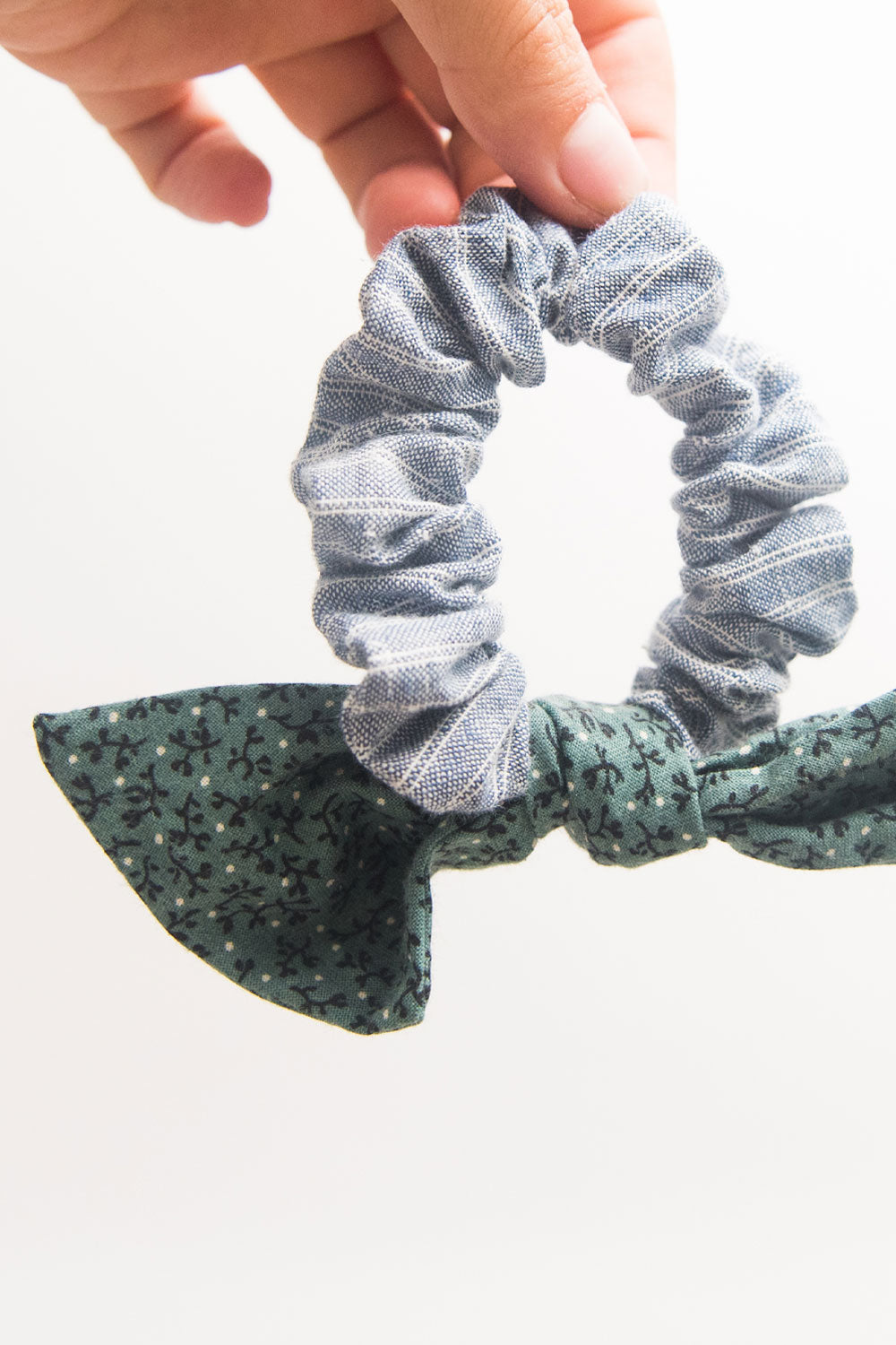 A blue and green bow hair scrunchie is held by two pinched fingers against white background.