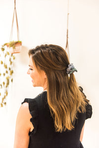 Back view of a woman with half her hair tied up with a bow hair scrunchie. Her head is turned to her left and she is smiling. Plants are hung from macrame in the background.