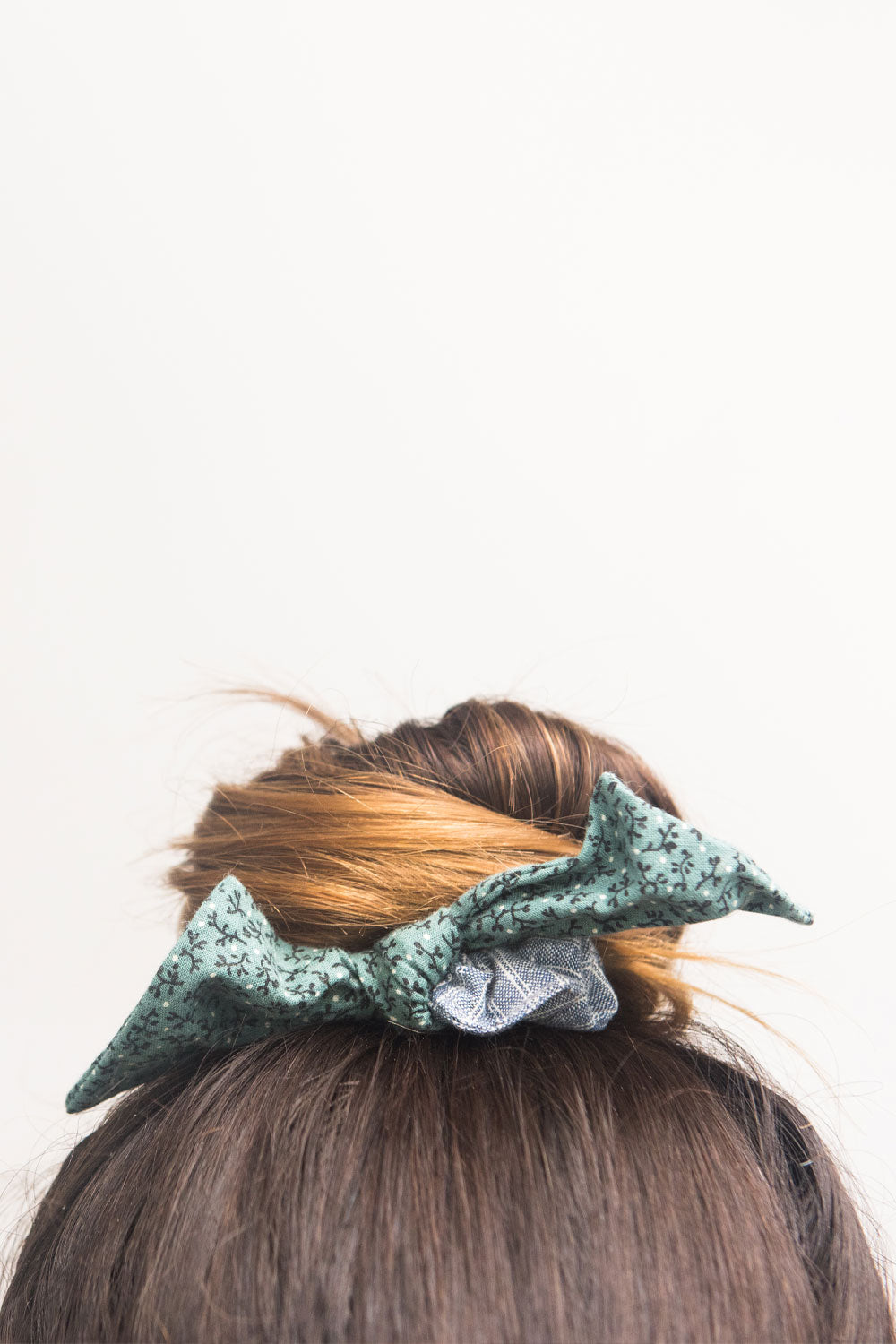 Close up of a woman's hair in a bun. She wears a blue and green fabric bow hair scrunchie.