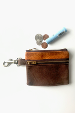 Load image into Gallery viewer, two zippered slim waxed canvas wallet with brass metal zippers and brass metal lobster claw clip at left side. Small orange printed fabric about 1/3 of wallet. Four coins and a chapstick lay next to the wallet for scale.