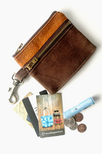 Load image into Gallery viewer, two zippered slim waxed canvas wallet with brass metal zippers and brass metal lobster claw at side. Small orange printed fabric about 1/3 of wallet. A few business cards, a chapstick, and 4 coins lay next to the wallet for scale.