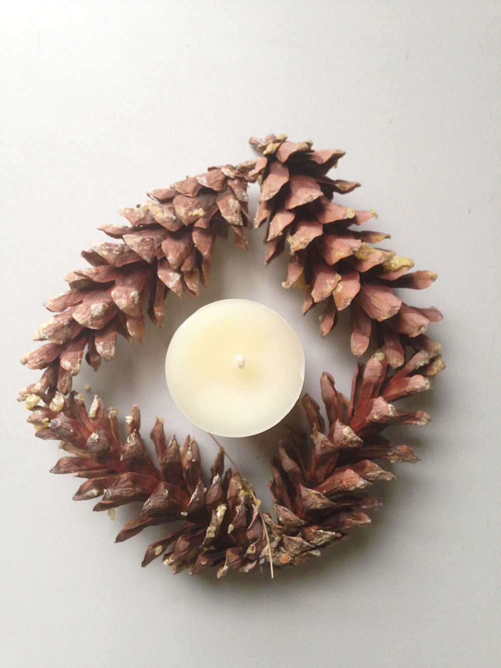 single beeswax votive candle surrounded by pinecones in circle