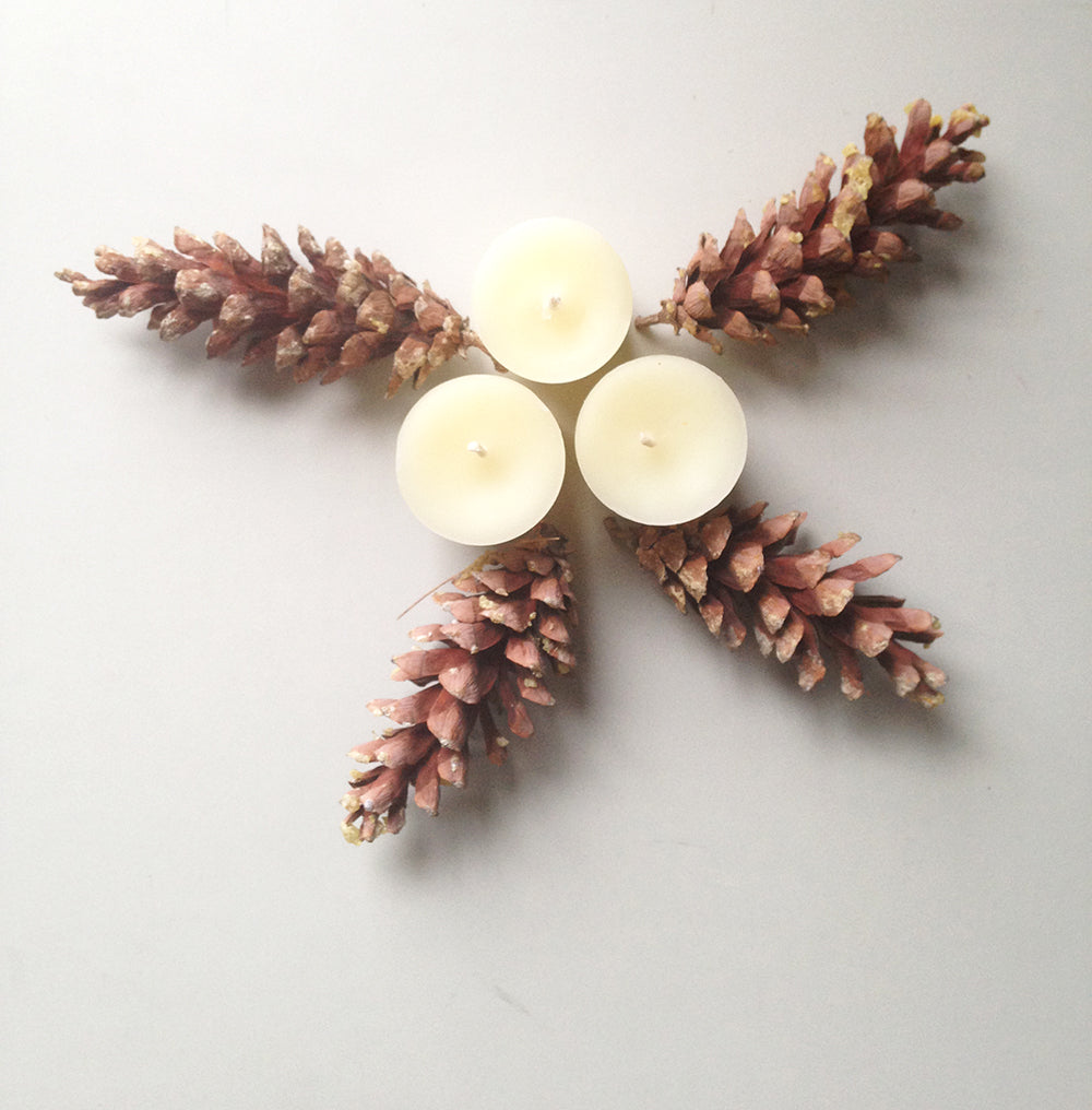 3 beeswax votive candles surrounded by 4 pinecones in star shape