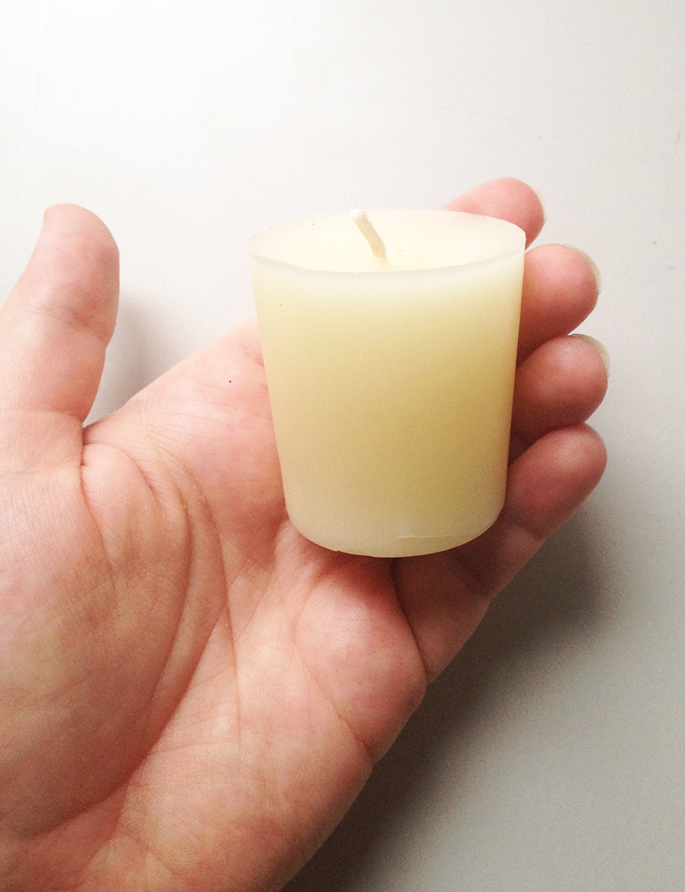 votive beeswax candle resting in hand