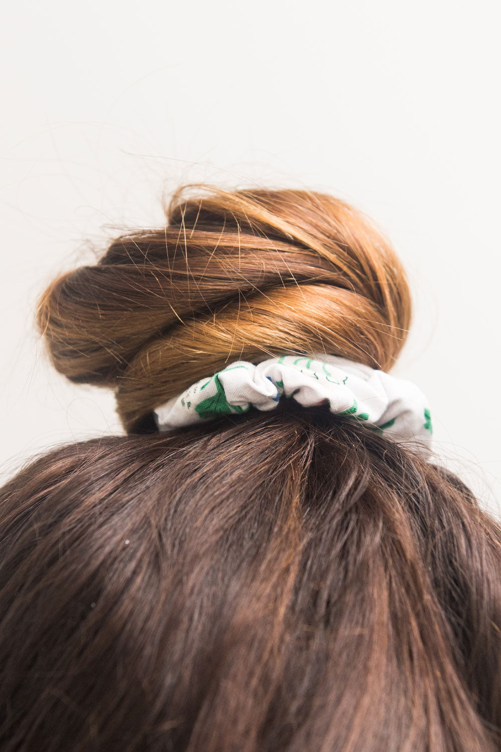a close up of a bun is tied off with a hair scrunchie
