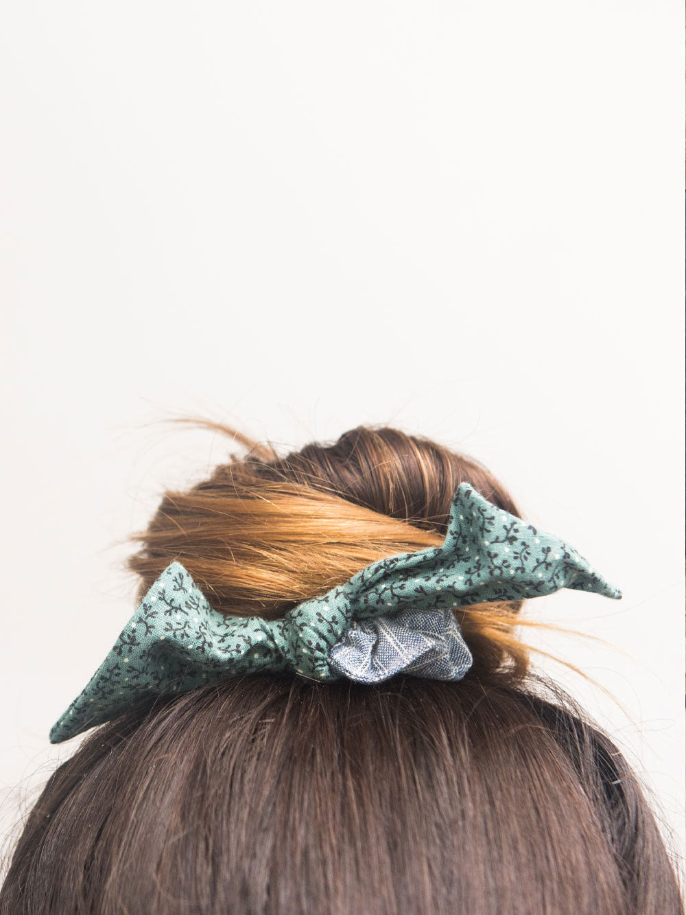 a close up of a bun is tied off with a bow hair scrunchie