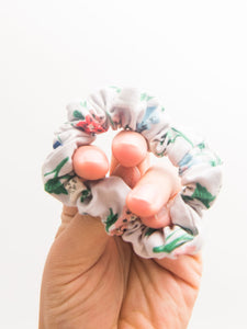 A close up of a scrunched up hand holds a classic hair scrunchie.
