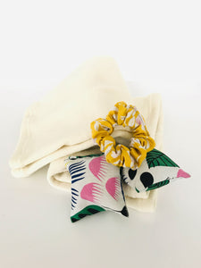 A classic hair scrunchie and pair of small square fabric hand warmers sit on a folded pair of cream leg warmers