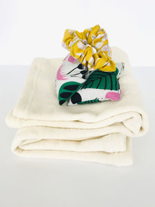A classic hair scrunchie sits on a pair of small square hand warmers, which sit on a pair of folded cream leg warmers.