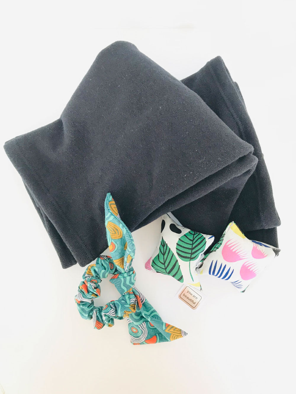 "A bow hair scrunchie sits next to a pair of small square fabric hand warmers which set next to a folded pair of black leg warmers. A small sticker with ""you are beautiful"" sits next to the hand warmers."