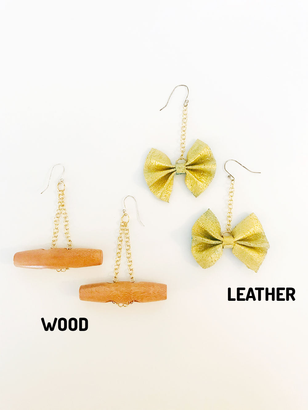 Two pairs of earrings on a white background. On the left: wood toggle buttons on gold inverted v-shape chain. Text below reads WOOD. On the right: gold painted leather bow on gold chain. Text below reads LEATHER.