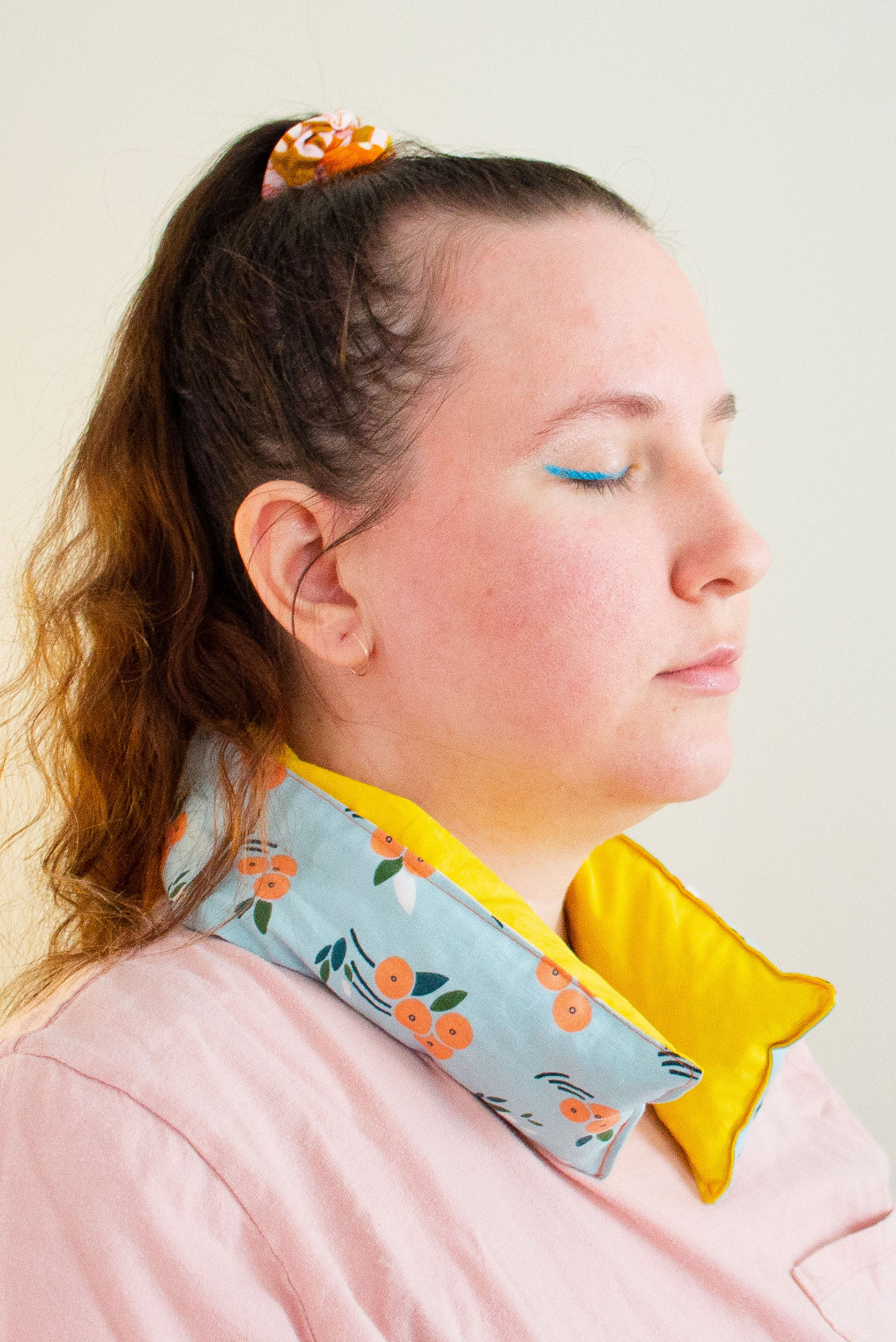 Profile of a woman with eyes closed wears a long and skinny cherry pit grain bag around her neck.