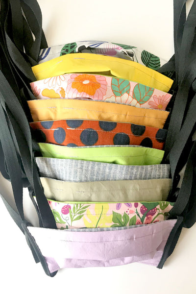 a row of cotton fabric face masks with black ties: various colors and floral or polka dot prints