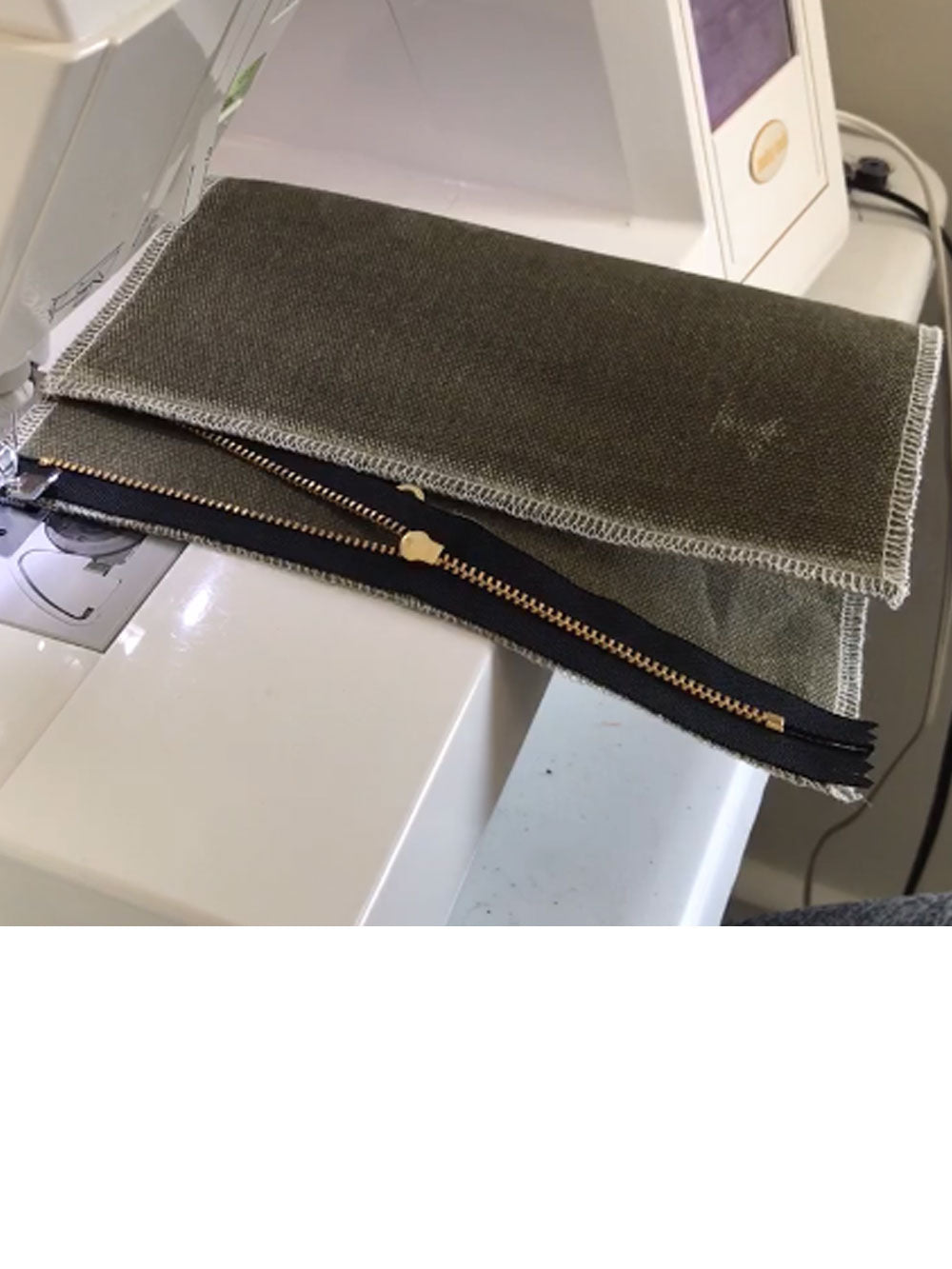 A zippered pouch in progress lays on a sewing machine.